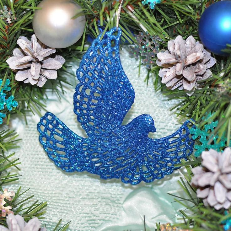 Новогодний венок Синяя птица. Рождественский венок  Венок создан из хвойных ветвей зеленого цвета украшен белыми шишками синими и серебряными шарами снежинками леденцами колокольчиками и синей птичкой. На венке присутствует лейбл мастерской съемный.  Размер: 40 см  Цена: 2500 руб