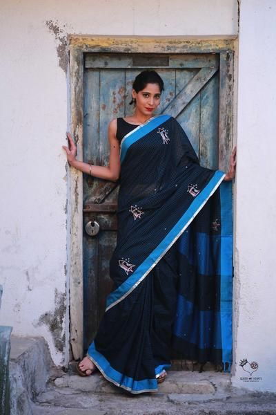 The Sky Collection Celebrating aeroplanes and rockets and flight. The Rockets Saree Inspired by ISRO.  Hand embroidered with silver and gold thread. Rockets and Stars on black/blue chequered Bengal cotton saree. Matched blouse included.  Material: Bengal Cotton Care: DRY CLEAN ONLY. Colour: Black/Blue Checks. Slight difference in colour from the visible product image is possible. Note: Blouse worn by model is not part of the saree. Delivery: Will be dispatched within 5 working days...