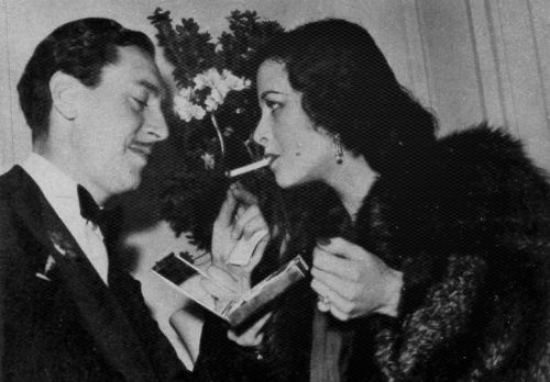 Reginald Gardiner lights a cigarette for Hedy