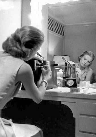 "Grace Kelly in her dressing room adjusting her Hermès ""Kelly"" during the filming of ""High Society,"" 1956."