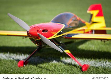 Ein ferngesteuertes Flugzeug steht auf dem Rasen. Gleich ist es bereit zum Abheben.