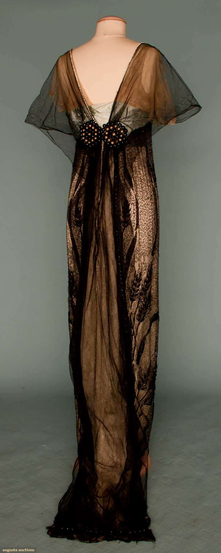 "WORTH EMPIRE EVENING GOWN, PARIS, c. 1912  Pale blue silk charmeuse covered w/ black silk tulle, sides embroidered in vermichelli pattern crystal beads, pattern interrupted w/ black bugle beads in swirling bands & sheaves of wheat, 2 large black & white jeweled rounds at CB, small square train, B 32"", H 37"", L 57""-71"", white silk petersham w/ white woven label Paris Worth"", inked on back ""4709"", (scattered holes in black tulle, nude tulle undersleeves torn, minor bead loss)"