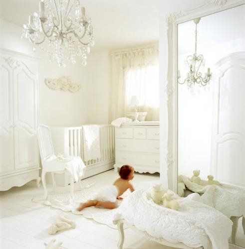 Scalloped hems, curved furniture, and a crystal chandelier give this all-white nursery a glamorous feel. A floor-to-ceiling mirror opens up the space even more while a gorgeous armoire keeps things traditional. Source: Chic Shack