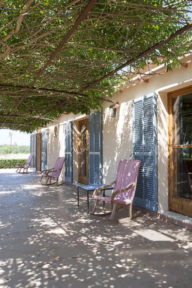 Mediterranean - Blue shutters and rocking chairs along a shaded pergola