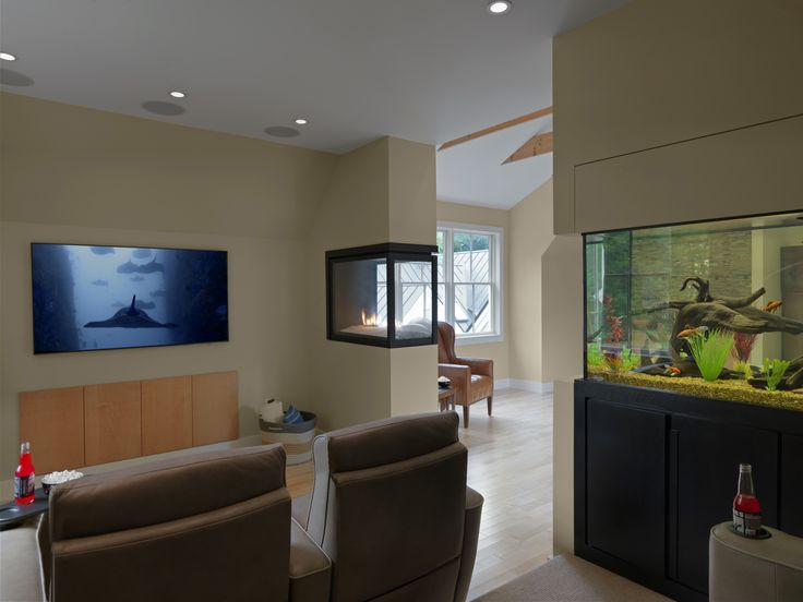 A 150 gallon fish tank built into a wall makes a splash in this media room and provides a subtle glow when ceiling lights are dimmed for the big screen. On the opposite wall a contemporary three-sided gas fireplace warms the room. With seating for four, the space is intimate and yet connected to the great room which includes a bar kitchenette and home office.   Design: Jillian Bartolo, Peregrine Design/Build  Photo: Susan Teare