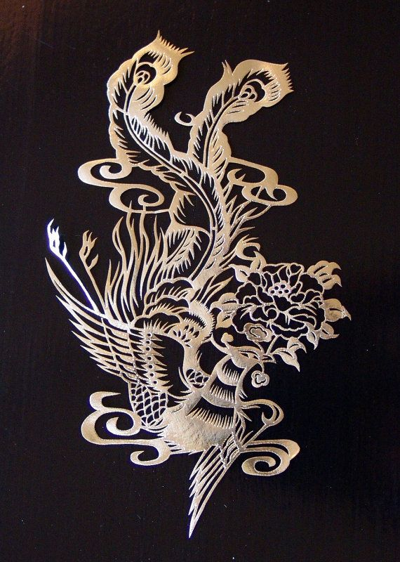 Golden Chinese paper cut showing a phoenix.                                                                                                                                                                                 More