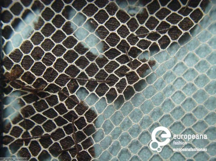Ondermouw in witte tule manchet en volant versierd met zwart fluwelen lint en machinale kant (imitatie Chantilly kloskant); op de volant applikaties in zwart fluweel; met draad omwikkelde knopen