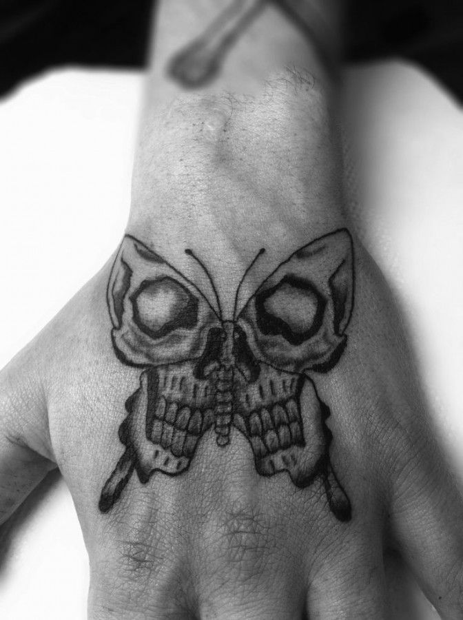 sick skull butterfly hand tattoo