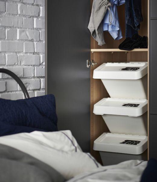 Drei gestapelte SORTERA Abfalleimer mit Deckel, die mit unterschiedlichen Waschtemperaturen beschriftet sind, stehen für das Sortieren von Schmutzwäsche in einem Kleiderschrank.