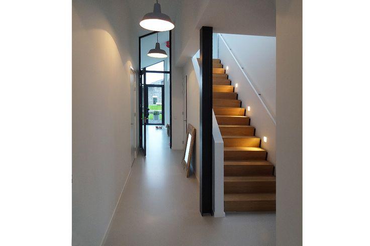 Strakke eiken trap met verlichting en gietvloer in nieuwbouwwoning in Nieuwkoop. Het ontwerp werd gemaakt door BNLA architecten uit Amsterdam.