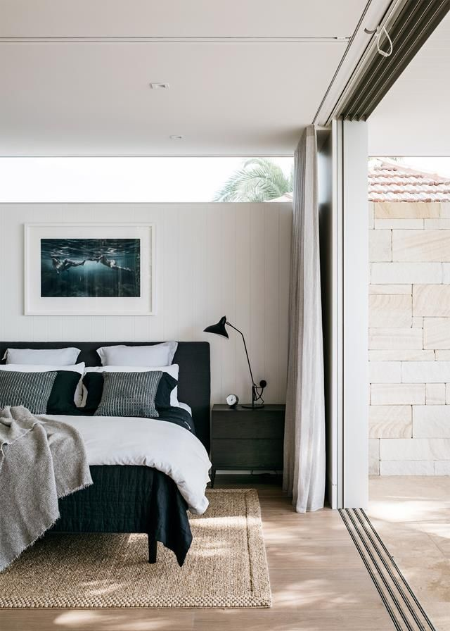 Floor to ceiling glass doors open up the master bedroom in this Palm Beach home to a private courtyard screened in by large-leafed plants. Photography: Felix Forest   Styling: Imogen Naylor   Story: Belle