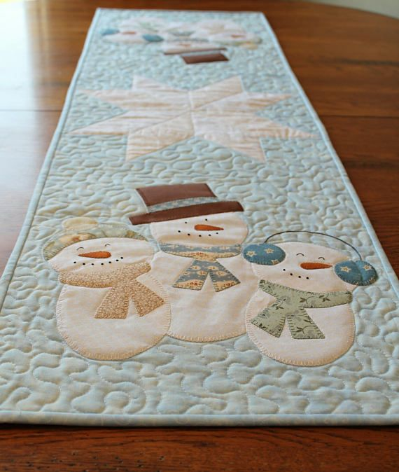 Snowman Table runner.           Add color, dimension and texture to your table decor. This Snowmen table runner will add just that to your table. It is made from 100% cotton, soft blues, tan/beige and white, colored fabric and measures 46 x 14. Sewing machine quilted in a meandering style and hand bound, it will look great on the dining room or kitchen table. **This ready made item will ship in 3-5 Business days. Makes a great gift.**