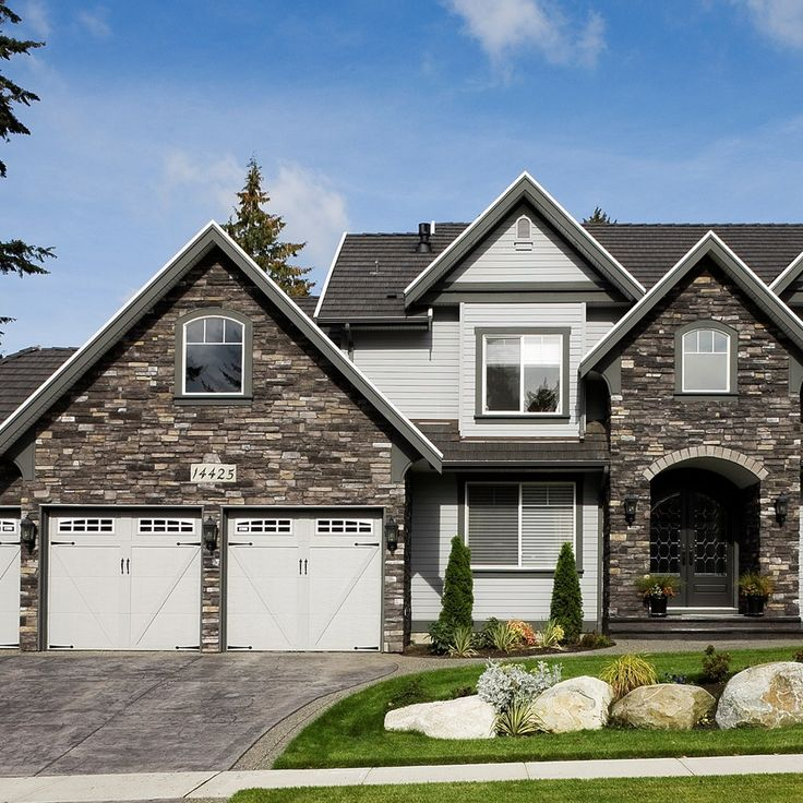 We love the contrast between the dark stone work and the light colored  siding and garage doors.