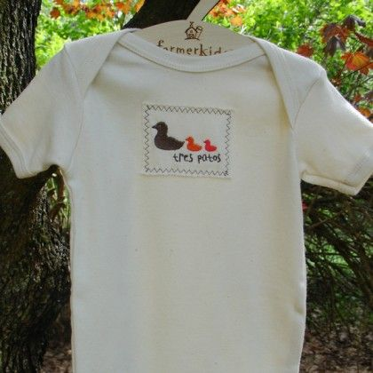"""One, two, three little ducks...or should we say """"uno dos tres patos""""... Our new little duck design has a mother duck and 2 baby ducks in brown, orange and bright red embroidery. Organic cotton patch is sewn on our 100% certified organic cotton infant tee or one piece. Color: Natural with brown, orange and bright red embroidery Made in USA Care: Machine wash cold, mild detergent, dry low heat. Iron on reverse side or between 2 pieces of cloth if necessary. Not intended for sleepwear"""