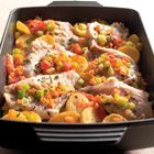 Roodbaars met worteltjes, tomaat en aardappelschijfjes uit de oven