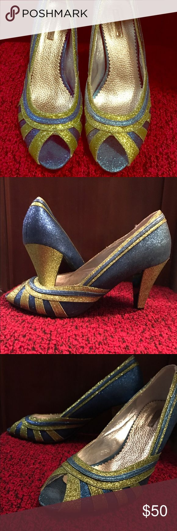 "WOW Fantastic Sparkling peep toe heels! You'll love the colorful combination and asymmetry in the coloring between the left and right shoe. The left shoe front and outer side have a royal blue and gold glittered sunburst type design. Inner portion of shoe is similarly designed but with silver and gold. The blue becomes silver in an ombré effect. The right shoe is blue and gold. Inside right shoe arch area outer side has 1"" tear. Some glitter thinning noted in a few spots but only obvious…"