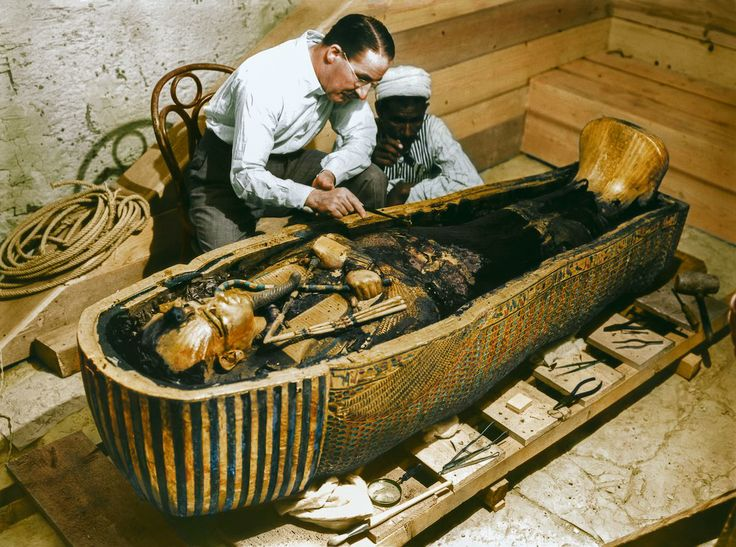 "October 1925 Carter and a worker examine the solid gold innermost sarcophagus. IMAGE: HARRY BURTON (C) THE GRIFFITH INSTITUTE, OXFORD. COLORIZED BY DYNAMICHROME FOR THE EXHIBITION ""THE DISCOVERY OF KING TUT"" IN NEW YORK."
