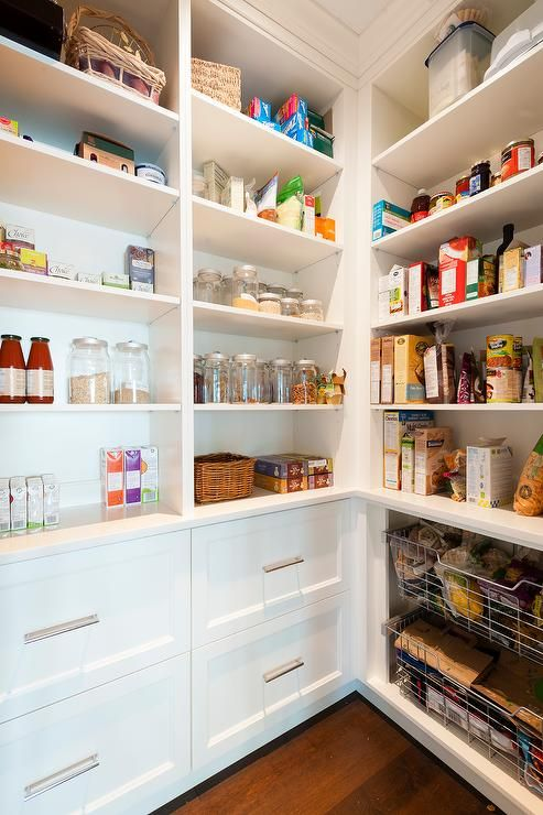 Fabulous walk-in pantry features white built-in shelves stacked atop drawers adorned with nickel pulls. Chic pantry boasts open shelving over stacked over wire pull out bins.