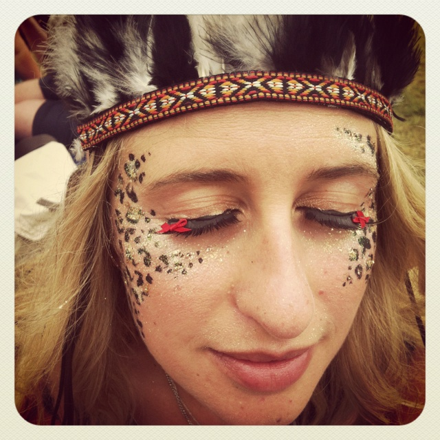 Leopard print face paint with glitter and bows on eyelashes - festival make-up