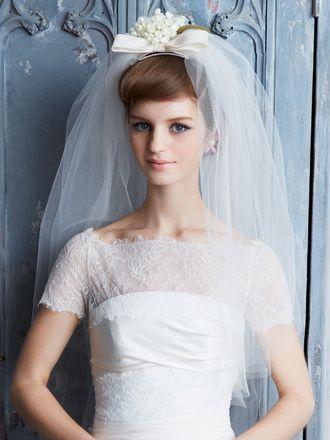 おしゃれ花嫁ヘア&ヘッドアクセ大図鑑 スグリ(正面) リボンとスズランが愛らしい主役級のベールは、ポンパドール風のヘアにつけてクラシカルかつモードに仕上げて。ベールの装飾に負けないフロントのボリューム感がおしゃれのカギ。