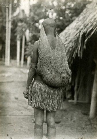 Sleeping baby in woven cradle hangs from mother's head - PNG