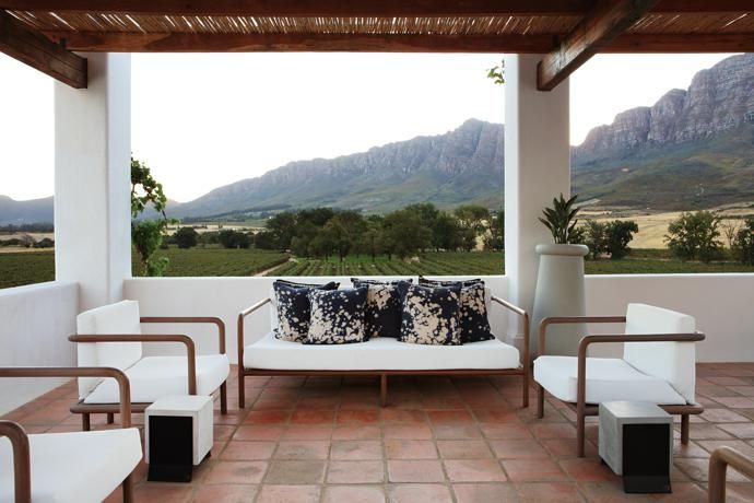 Contemporary patio furniture by Meyer Von Wielligh brings a modern feel to the more- than-300-year-old farm. The patio overlooks vineyards and the eastern slopes of Saronsberg.