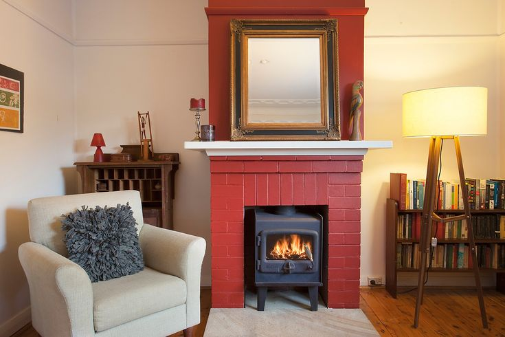 Lounge room, slow combustion fireplace, floor lamp, sitting chair, mirror, book collection, Pilcher Residential