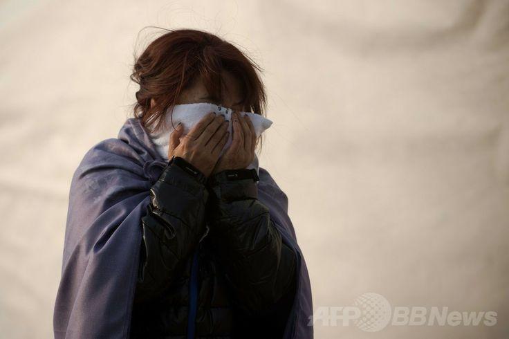 韓国南西部・珍島(Jindo)で涙を流す、沈没した旅客船セウォル(Sewol)号の乗客の家族(2014年4月21日撮影)。(c)AFP/Nicolas ASFOURI ▼22Apr2014AFP|韓国船沈没、携帯アプリの通信分析で当時の状況把握へ http://www.afpbb.com/articles/-/3013213