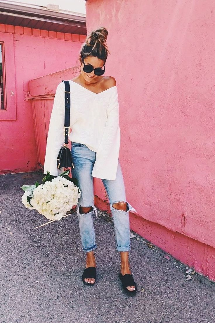 Off the shoulder white sweater with trendy distressed denim jeans.