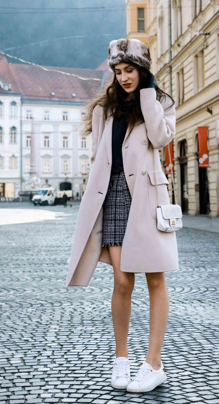 Fashion Blogger Veronika Lipar of Brunette from Wall Street wearing white sneakers from Diesel, black and white plaid tweed mini skirt from Storets, black silk blouse from Juicy Couture, off-white double breasted wool coat from MaxMara, faux fur headband, white shoulder bag with gold chain strap, blue leather gloves on the street in Ljubljana