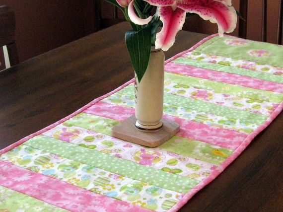 Here comes Peter Cottontail, hopping down the bunny trail! This adorable quilted table runner will bring spring and smiles to your Easter dinner! Strips of 100% cotton with little eggs, bunnies, chicks and polk dots coordinate perfectly with the polyester backing, and everything is highlighted with stitching of hot pink. Perfectly matched hot pink ribbon peeks out from the hem-stitching around the edges of each end.    Each end also has 3 little bunnies fussy-cut & appliqued to the solid…