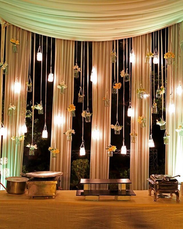 Isn't this the prettiest thing you have seen today ? Mason jars with fairy lights and glass bottles with flowers | Decor by @the_flagship_store | #decor #floralwall #indianbride #indianwedding #decor #weddingdecor #hanginglamps #stagedecor #candledecor