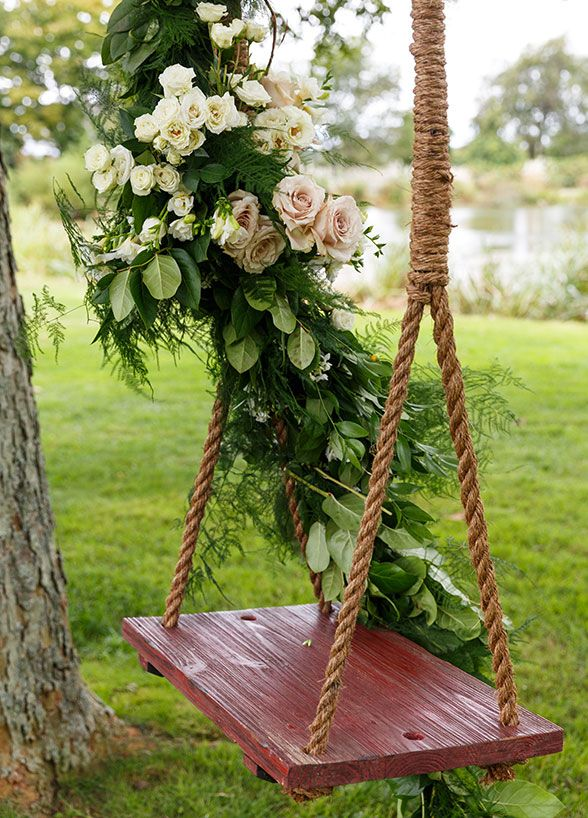 Beautiful flowers and leaves decorated the swing. Cute idea for an spring/summer outdoor garden wedding.
