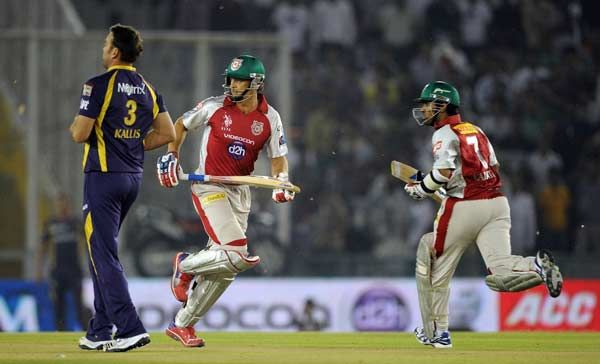 Kolkata Knight Riders bowler Jacques Kallis watches as Kings XI Punjab batsmen Paul Valthaty (R) and Adam Gilchrist run between the wickets during the the IPL Twenty20 cricket match between Kings XI Punjab and Kolkata Knight Riders at PCA Stadium in Mohali on April 18, 2012.