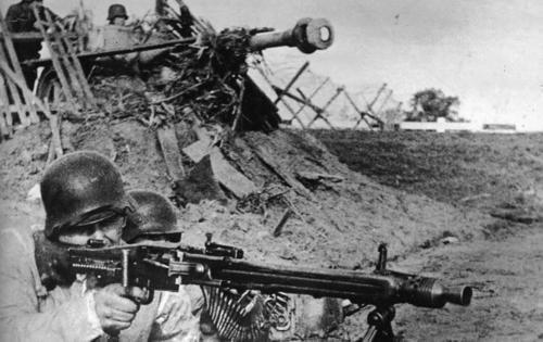 MG-42 machine gun crew 88 mm gun in the background