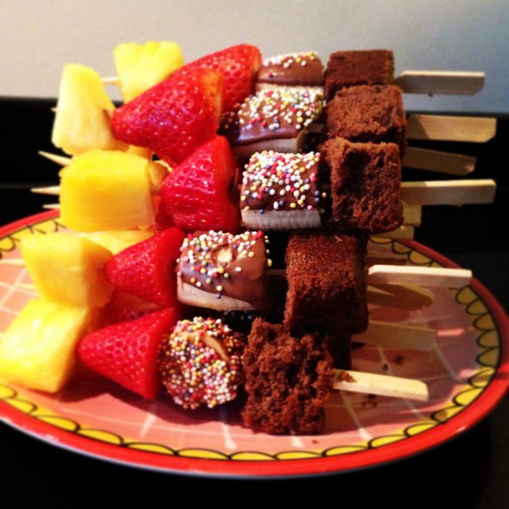 Traktatie: tapas spies met blokje chococake, stukje banaan gedoopt in chocola met spikkels erover, aardbei en verse ananas