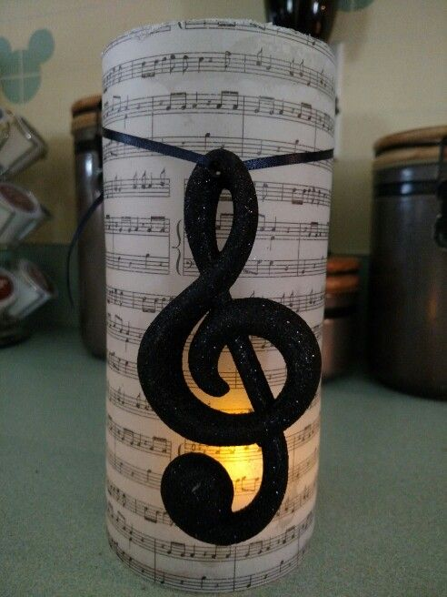 Vellum Music Sheet Candle. It is wrapped around a glass cylinder. Also has very fine white iridescent glitter around the top lip.