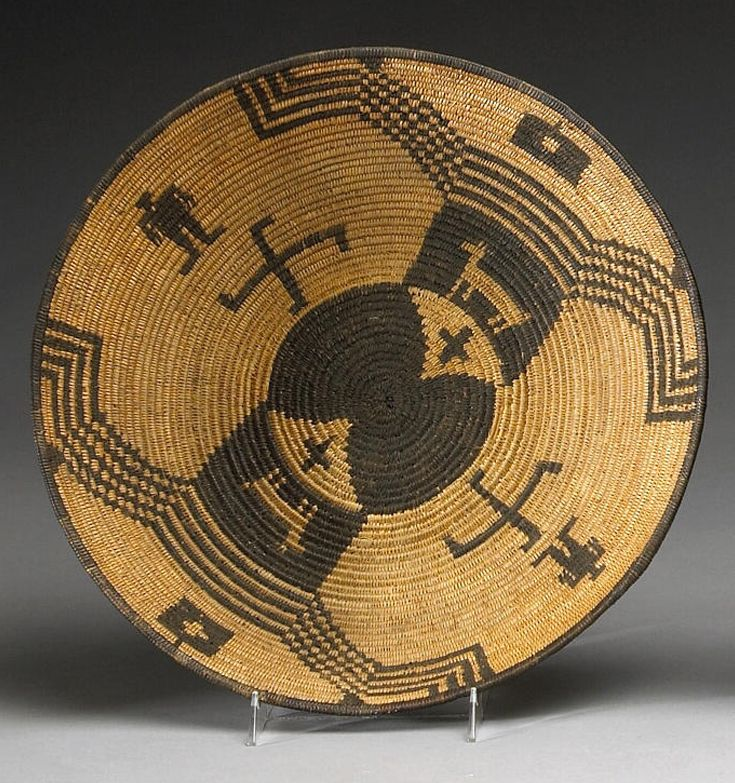An Apache tray | Finely woven and showing an hourglass figure and cross motifs on the base, flanked by opposing compositions of negative deer images and bidirectional linear appendages, human figures, whirling log motifs and box devices as accents.