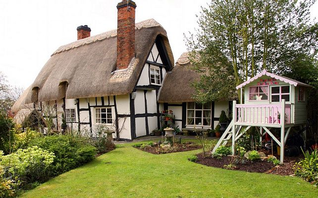 Located in an olde-world village in the Birlingham, Worcestershire, UK, this rental English thatched cottage is perfect for families or couples looking for a romantic place to stay. Look at the playhouse!