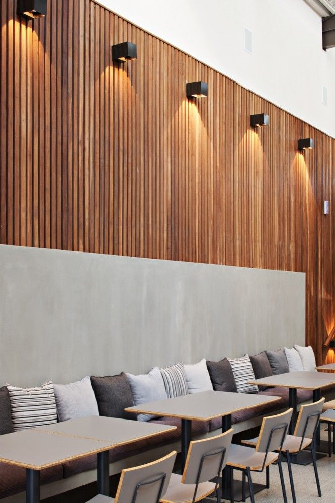 Slim timber strip wall mounted to create this image- modern square down lighters used to contrast  the dark timber. Wall opposite the bar