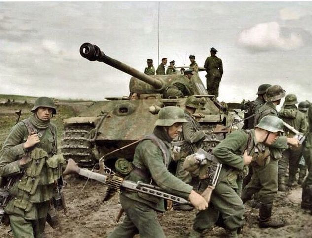 """Panzergrenadiers from the 131st. Infantry Division (Wehrmacht) tramping through churned up fields of mud to advance near the battlefield. The Panzer V (Panther) that they are passing by is a command tank belonging to the 5th SS Panzer Division """"Wiking"""". Note on top of the tank is SS Obersturmbannführer Johannes Mühlenkamp. Kovel, Ukraine, 1944"""