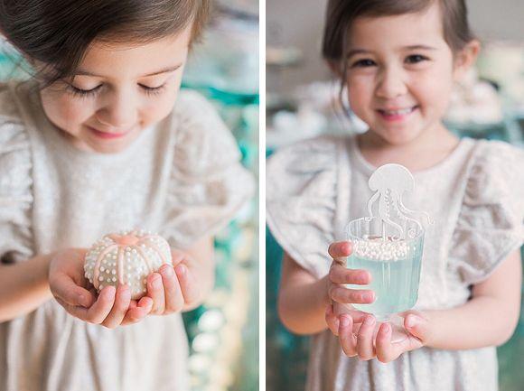 Une enfant regarde les gâteaux et boissons de son anniversaire océan