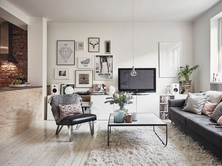 metalowy stolik kawowy,czarny fotel na metalowych nóżkach,grafitowa sofa,białe szafki TV z galerią grafik na białej ścianie - Lovingit.pl