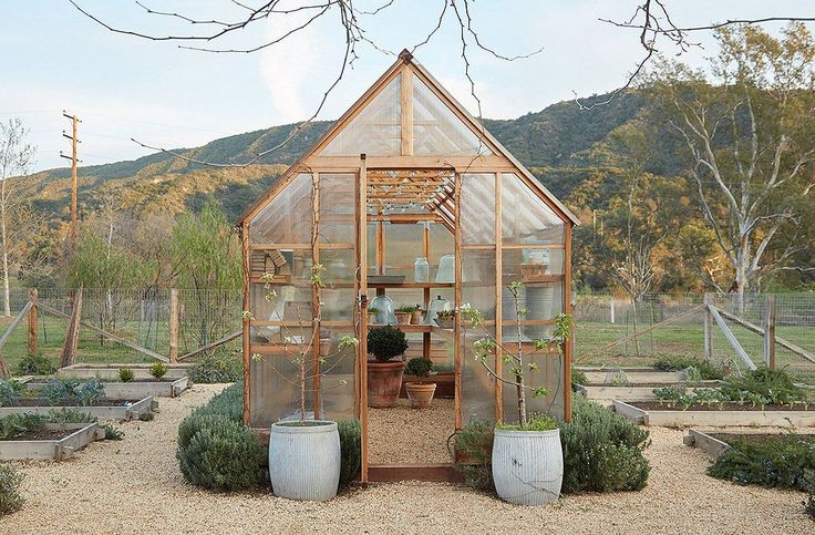 """Gardens and animals were always part of the plan. """"We envisioned eating our chickens' fresh eggs and cooking with the vegetables and fruits we would grow,"""" says Brooke. The prefabricated greenhouse has shelves to protect delicate plants and start seedlings. A miniature hedge of rosemary grows around the perimeter."""