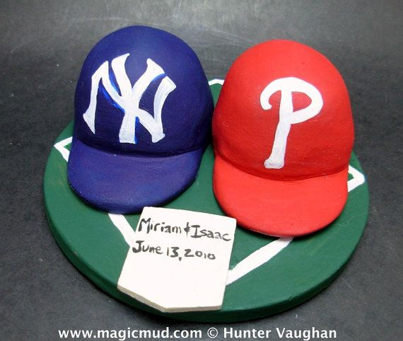 Baseball Hat Wedding Anniversary Gift, New York Yankees Wedding CakeTopper, Baseball Wedding Anniversary Gift    Wedding Cake Topper for MLB Baseball Fans, custom created for you! Perfect for the marriage of a Red Sox, or any baseball team, loving Groom and his Bride! Simply email or call toll free with your own info and pictures of yourselves, and we will sculpt for you a treasured memory from your wedding!    $235 #magicmud 1 800 231 9814 www.magicmud.com