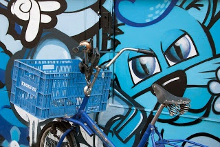 Bike with blue basket in front of a blue painted wall in Amsterdam.