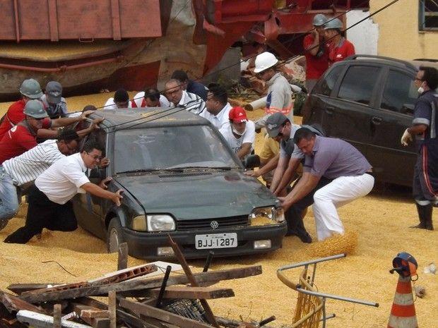 Moradores retiram carro atingido pelo vagão para facilitar acesso dos bombeiros (Foto: Marcos Lavezo/G1)