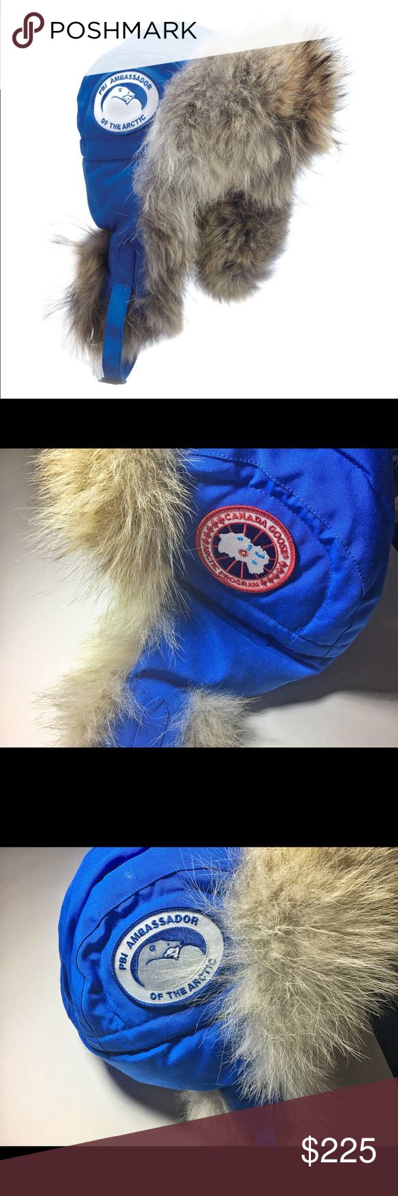 """Canada Goose PBI Aviatoe Hat L/XL """"Turn-of-the-century pilot style with modern-day durability and warmth""""  Style #: 5187MPB  FILL: 625 Fill Power White Duck Down  Features: Water-resistant Arctic-Tech fabric exterior for durability and weather-resistance, Coyote fur ruff visor and ear-flaps are a turn-of-the century functional feature that kept pilots warm in an open cockpit at high speeds, Adjustable buckle chin strap for high-wind conditions, Polar Bears International patch on right side…"""