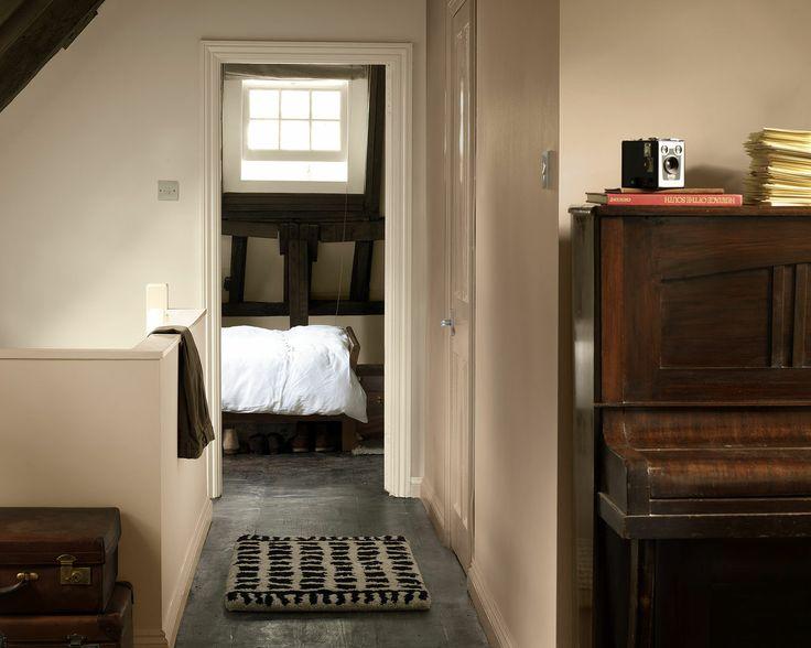 Illuminez les tons terreux avec des teintes crème. La teinte pierre des murs et le sol du couloir contrastent de façon rafraîchissante avec les poutres de chêne sombre et le piano acajou.