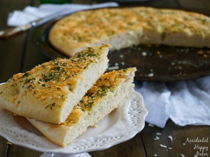 Light and tender homemade focaccia bread, topped with butter, garlic, cheese and herbs.